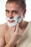 Attractive man shaving his face Stock Image