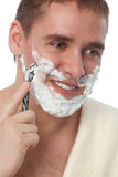 Attractive man shaving his face Royalty Free Stock Images