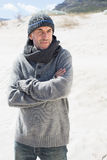 Attractive man shivering on the beach in hat and scarf Stock Photos