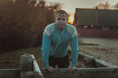 Attractive man sitting on  beach in the evening sunset after sport Stock Photography