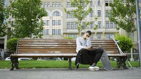 Young man sitting on the bench in the park listening to music on his cellphone. Crutches and skateboard are nearby. Attractive man sitting on the bench in summer stock video