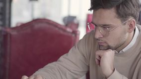 Portrait of handsome guy sitting in a cafe, waiting for his order or in hub and working intently at the computer. Attractive man is sitting in a cafe, waiting stock video footage
