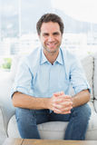 Attractive man sitting on the couch smiling at camera Stock Photos