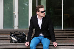 An attractive man sitting down outside wearing jeans and a blazer Royalty Free Stock Photography