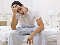 Attractive Man Sitting on His Bed Yawning royalty free stock photo