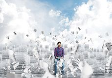 Attractive man sitting on pile of paper documents. Young man in casual clothing sitting on pile of documents among flying papers with cloudly skyscape on Stock Photos