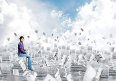 Attractive man sitting on pile of paper documents. Young man in casual clothing sitting on pile of documents among flying papers with cloudly skyscape on Royalty Free Stock Image