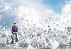 Attractive man sitting on pile of paper documents. Young man in casual clothing sitting on pile of documents among flying papers with cloudly skyscape on Stock Photo