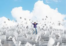 Attractive man sitting on pile of paper documents. Young man in casual clothing sitting on pile of documents among flying papers with cloudly skyscape on Stock Photography