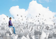 Attractive man sitting on pile of paper documents. Royalty Free Stock Image