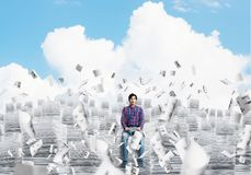 Attractive man sitting on pile of paper documents. Young man in casual clothing sitting on pile of documents among flying papers with cloudly skyscape on Royalty Free Stock Photography
