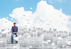 Attractive man sitting on pile of paper documents. Stock Images
