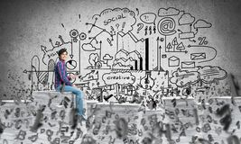 Attractive man sitting on pile of paper documents. Young man in casual wear sitting among flying letters with business-analytical information on background Royalty Free Stock Photography