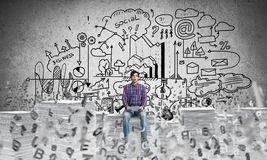 Attractive man sitting on pile of paper documents. Young man in casual wear sitting among flying letters with business-analytical information on background Royalty Free Stock Photo