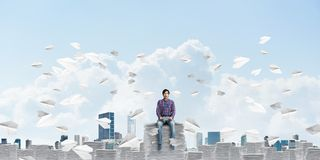 Attractive man sitting on pile of paper documents. Stock Image