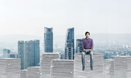 Attractive man sitting on pile of paper documents. royalty free stock photo