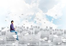 Attractive man sitting on pile of paper documents. Young man in casual clothing sitting on pile of documents among flying paper planes with cloudly skyscape on Stock Photo