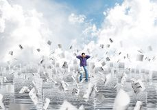 Attractive man sitting on pile of paper documents. Young man in casual clothing sitting on pile of documents among flying papers with cloudly skyscape on Stock Images
