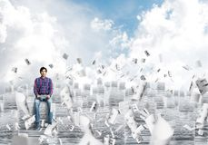 Attractive man sitting on pile of paper documents. Young man in casual clothing sitting on pile of documents among flying papers with cloudly skyscape on Stock Image