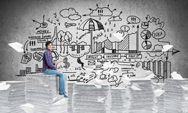 Attractive man sitting on pile of paper documents. Young man in casual wear sitting among flying paper planes with business-analytical information on background Stock Photography
