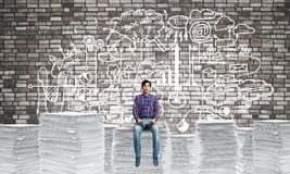 Attractive man sitting on pile of paper documents. Young man in casual wear sitting on pile of documents with business-analytical information on background Royalty Free Stock Photography