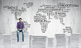 Attractive man sitting on pile of paper documents. Young man in casual wear sitting on pile of documents with business-related terms in form of world map on Stock Images