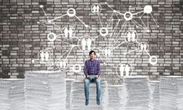 Attractive man sitting on pile of paper documents. Young man in casual wear sitting on pile of documents with social network structure on background. Mixed Royalty Free Stock Image