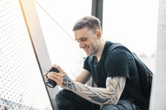 Attractive man sitting at staircase, smiling and checking photos in camera. royalty free stock photo