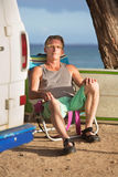 Attractive Man Sitting with Surfboard Stock Photo