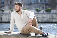 Attractive man is sitting on a wall in berlin. Near by a river Royalty Free Stock Photography