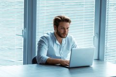 Attractive man sitting working at a laptop royalty free stock photography