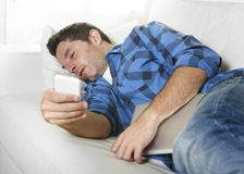 Attractive man sleeping at home couch with mobile phone and digital tablet pad in his hands. Young attractive man in shirt and jeans sleeping at home couch with Stock Photo