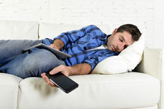 Attractive man sleeping at home couch with mobile phone and digital tablet pad in his hands. Young attractive man in shirt and jeans sleeping at home couch with Royalty Free Stock Photography