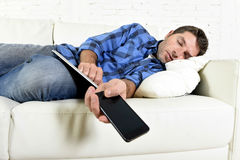 Attractive man sleeping at home couch with mobile phone and digital tablet pad in his hands. Young attractive man in shirt and jeans sleeping at home couch with Royalty Free Stock Image