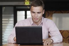 Attractive man with a smile work on laptop Stock Images