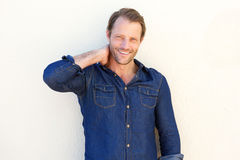 Attractive man smiling against white wall Royalty Free Stock Image
