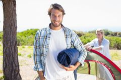 Attractive man smiling at camera while partner pitches tent Royalty Free Stock Image