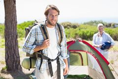 Attractive man smiling at camera while partner pitches tent Royalty Free Stock Photos