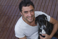 Attractive man smiling with dog Royalty Free Stock Images