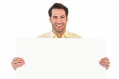 Attractive man smiling and holding poster. On white background Stock Image