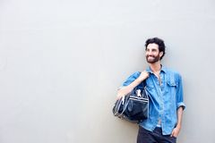 Attractive man smiling and holding travel bag over shoulder Stock Photos
