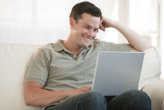 Attractive Man Smiling with Laptop Royalty Free Stock Photos