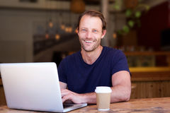 Attractive man smiling with laptop at cafe. Portrait of attractive man smiling with laptop at cafe Royalty Free Stock Photo