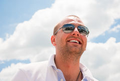 Attractive man smiling. Attractive man laughing against blue sky Royalty Free Stock Photos