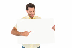 Attractive man smiling and pointing white poster. On white background Stock Photos