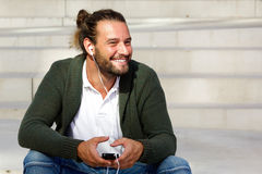 Attractive man smiling with smart phone and headphones Stock Images