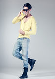 Attractive man smiling talking on a yellow phone Royalty Free Stock Photography