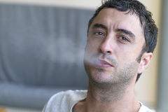 Attractive man smoking a cigarette Stock Images