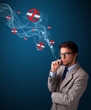 Attractive man smoking dangerous cigarette with no smoking signs Royalty Free Stock Photo