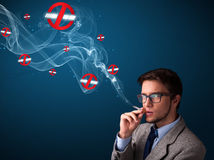 Attractive man smoking dangerous cigarette with no smoking signs Stock Photos